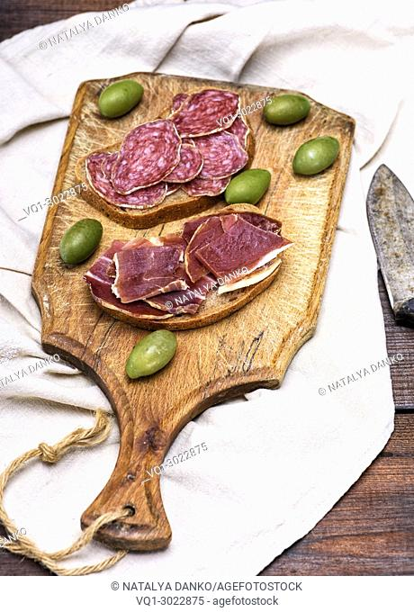 sandwiches with hamon and smoked sausage salami on a wooden board