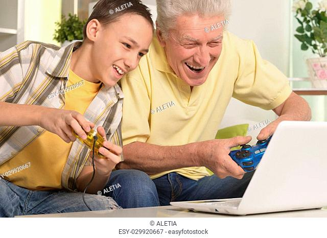 portrait of boy and grandfather with a laptop,playing computer game at home