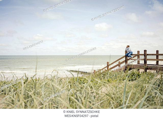 Woman sitting on fence at the beach, relaxing at the sea