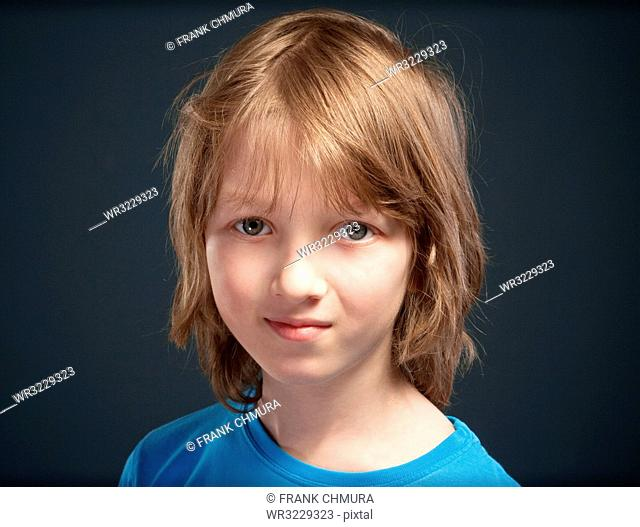 Portrait of a Boy with Long Blond Hair in Blue Top