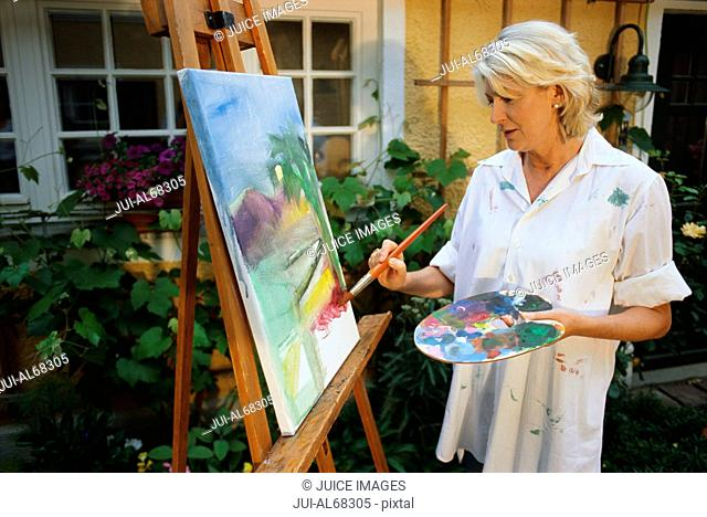Mature woman painting on an easel outdoors