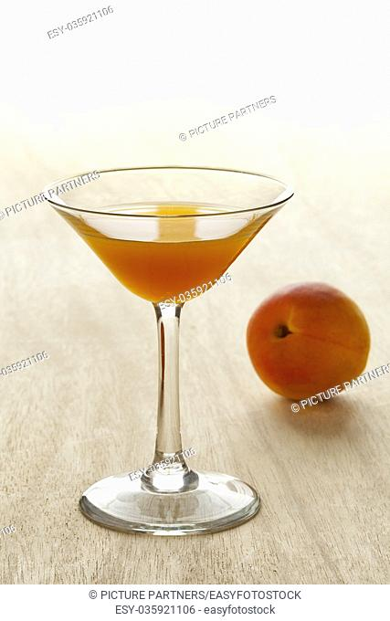 Glass of apricot liqueur and fresh fruit on the background