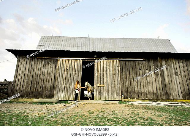 Young Woman Leading Horse out of Barn