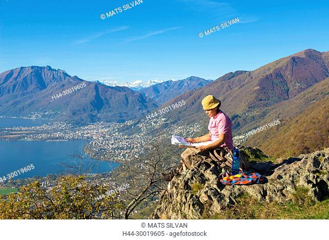 Woman Reading Map On Mountain Top in Ticino, Switzerland