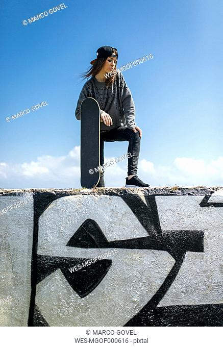 Portrait of young skateboarder wearing baseball cap standing on a wall