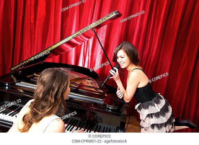 Two women singing a duet with a concert piano, having fun together