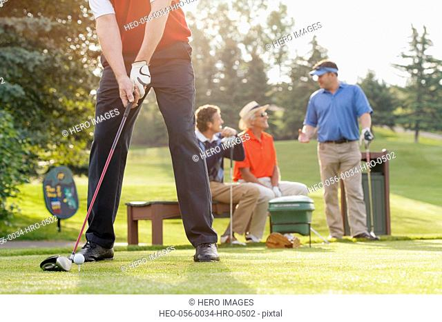 middle-aged golfer ready to drive ball off tee-box