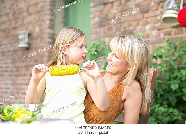 Mother With Daughter Eating Sweetcorn At Home In Garden