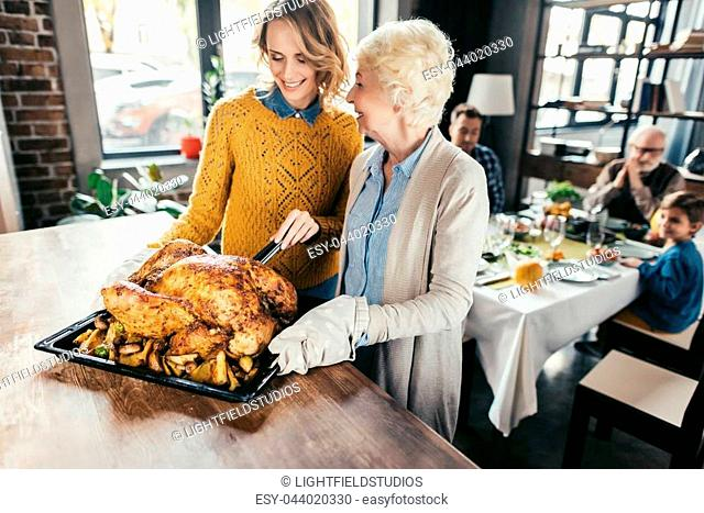 smiling senior mother and daughter with thanksgiving turkey for family dinner