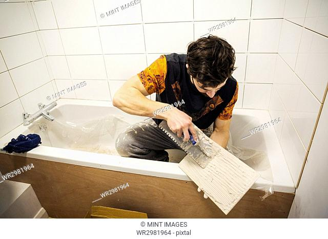A builder, tiler sitting in a bathtub spreading adhesive on a tile
