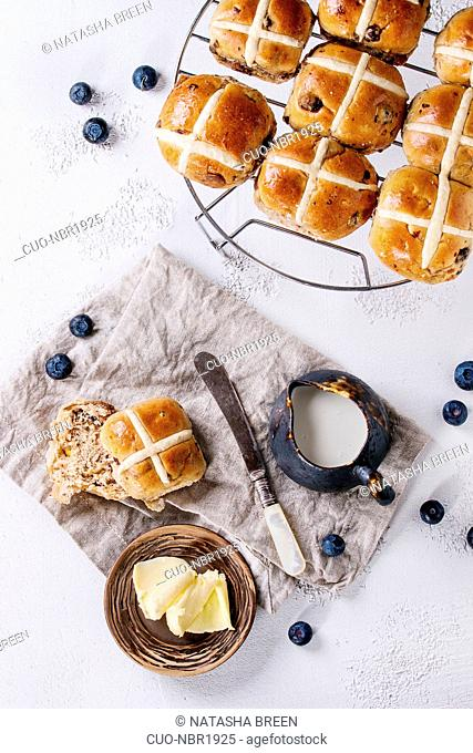 Hot cross buns on baking rack served with butter, fresh blueberries, knife and jug of cream on textile napkin over white texture concrete background
