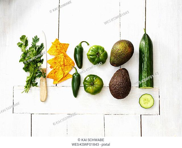 Avocados, green tomatoes, Jalapeno peppers, cucumber, parsley, kitchen knife and tortilla chips on white wood