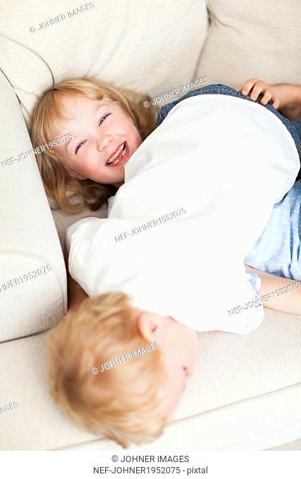 Brother and sister playing on sofa, Sweden
