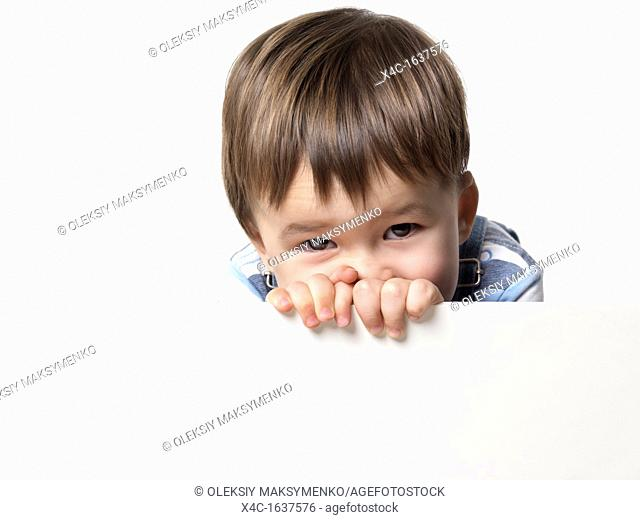 Two year old boy behind a white sign isolated on white background with copyspace