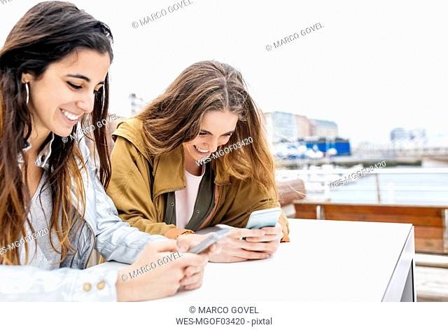 Two happy young women sending messages with their smartphones