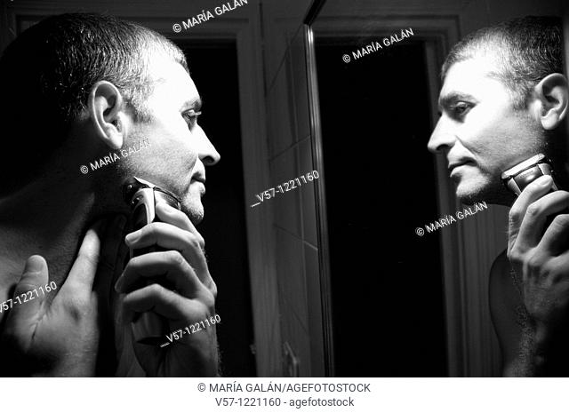 Man shaving his face in front of mirror. Black and white