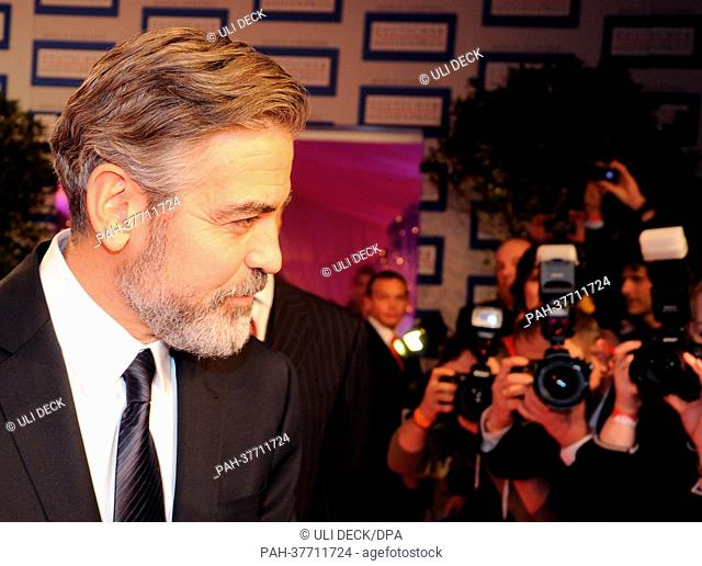 US actor George Clooney poses after receiving the German Media Prize 2012 at the award ceremony with Karlheinz Koegel of Media Control in Baden-Baden, Germany