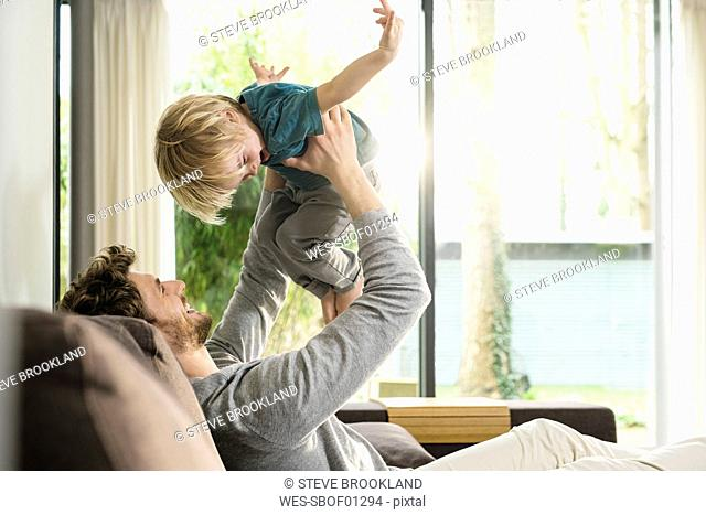 Happy father playing with son on sofa at home