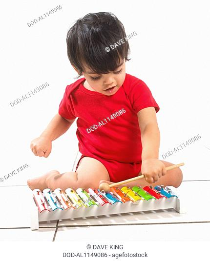 Small boy (16 months) playing xylophone