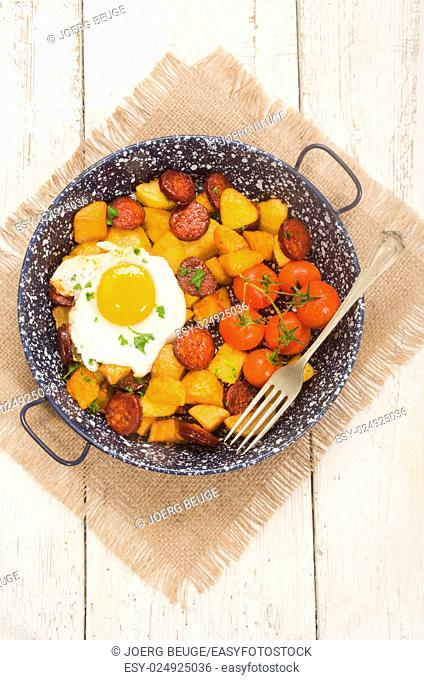 spanish country style meal with potato, cherry tomato, fried egg, parsley and chorizo in a pan