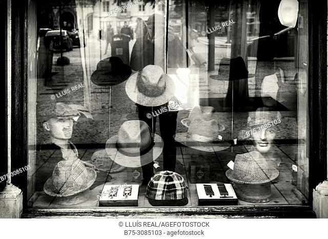 Shop window of a shop of hats with the image of the photographer reflected in the glass. Lisbon, Portugal