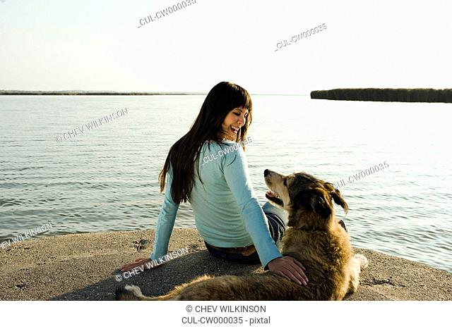 Woman sitting by lake with dog