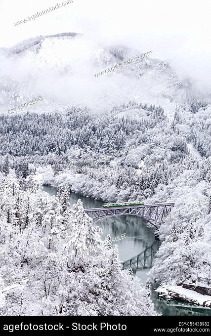Winter landscape snow covered trees with train crossin River on Bridge