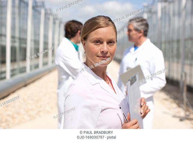 Scientist holding clipboard in greenhouse