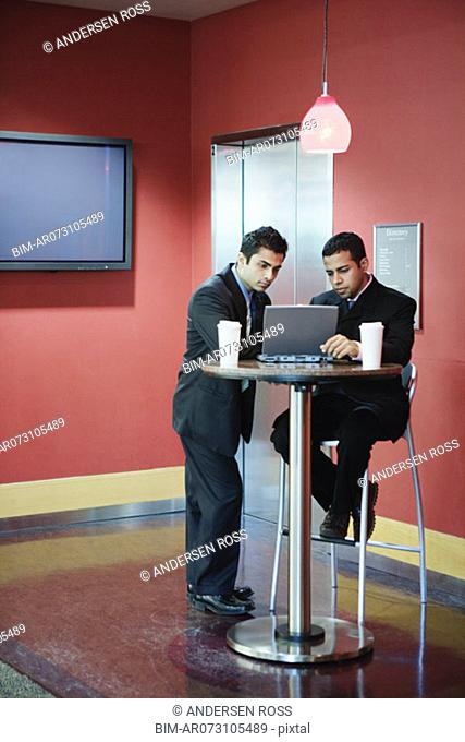 Two men working on laptop