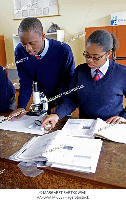 School children using microscope in school lab, St Mark's School, Mbabane, Hhohho, Kingdom of Swaziland