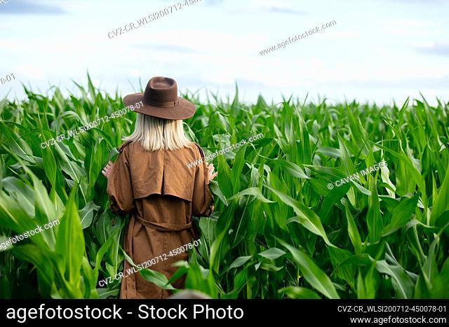 Blonde woman in cloak and hat in cornfield in summertime