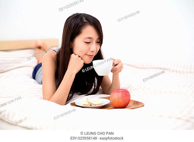 Woman lying down on having breakfast