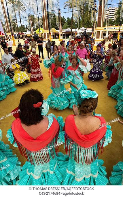 Women wearing beautifully coloured gypsy dresses perform traditional Andalusian dances at the Feria del Caballo (Horse Fair) in Jerez de la Frontera