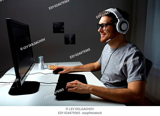 technology, gaming, entertainment, let's play and people concept - happy young man in headset and glasses with pc computer playing game at home and...