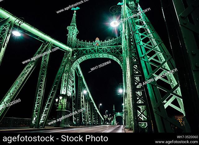 Old Iron Bridge at night in the light of streetlights across the Danube River in Budapest Hungary