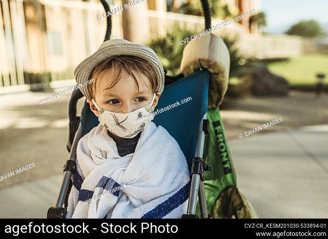 Close up portrait of young boy with mask on outside on vacation