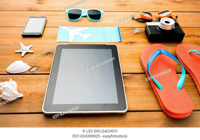 vacation, travel, tourism, technology and objects concept - close up of tablet pc computer and travel stuff