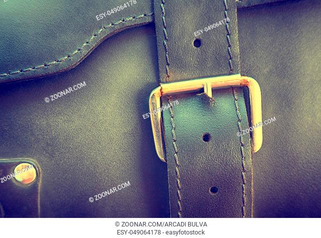 Texture of a black portfolio with a genuine leather buckle with embossed, close-up, texture for a designer, background, selective focus, retro style