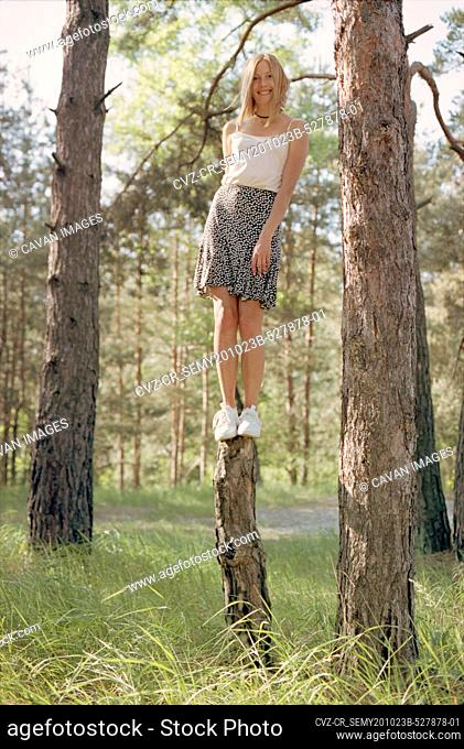 Blond woman in a skirt standing on a log in the spring forest