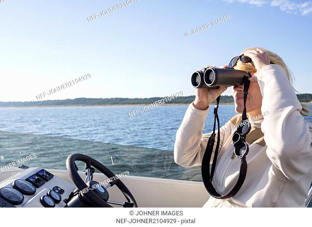 Woman on boat looking through binoculars