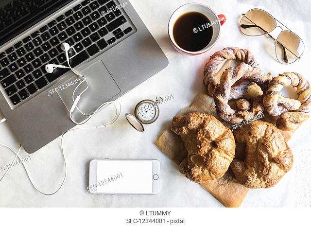 Breakfast in the office with cup of coffee and sweet pretzels