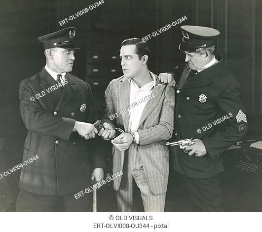 Man taken into custody by two policemen (OLVI008-OU344-F)