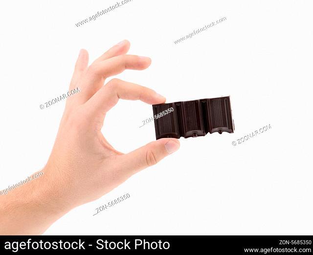 Hand holds tasty morsel of dark chocolate. White background