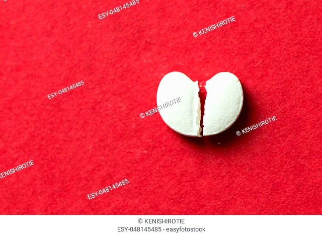 Broken heart shaped pill isolated on red background