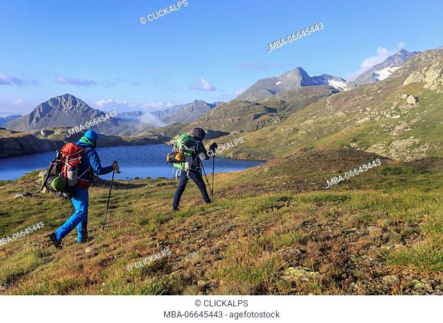 Hikers admire the peaks and the blue alpine lake Minor Valley High Valtellina Livigno Lombardy Italy Europe