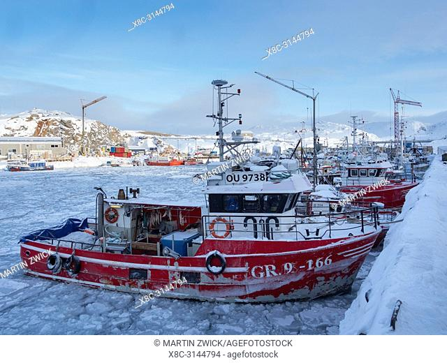 The frozen harbour with fishing boats. Town Ilulissat at the shore of Disko Bay in West Greenland, center for tourism, administration and economy