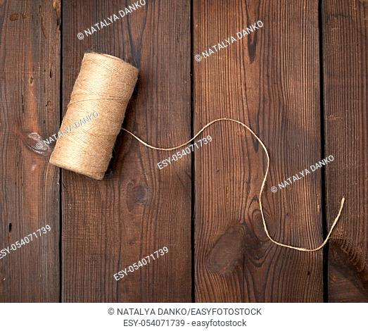 brown thread twisted into a spool on a wooden background, eco products