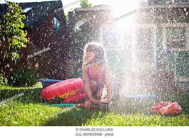 Young girl playing in garden sprinkler