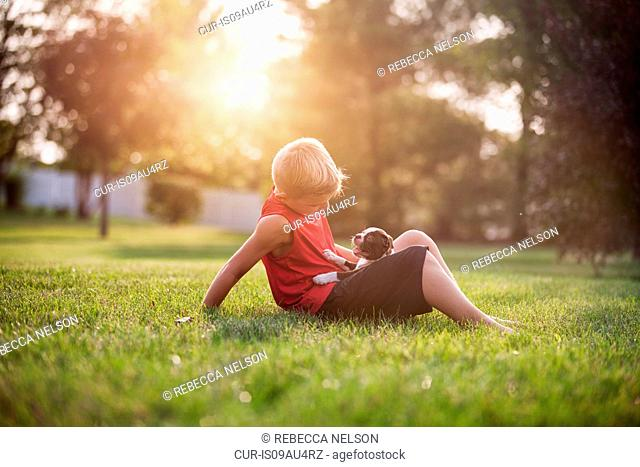 Side view of boy sitting on grass, Boston Terrier puppy on lap, looking down