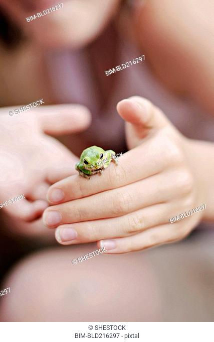 Caucasian girl playing with frog